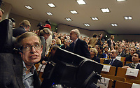 (dpa) - Handicapped British physician Stephen Hawking (L) sits in his wheelchair in an overcrowded lecture hall of the 'Freien Unversitaet' University Berlin, Germany, Monday 17 October 2005. Stephen Hawking lectured in the 'Einstein Lectures' programme. Credit: Steffen Kugler/DPA /MediaPunch ***FOR USA ONLY***