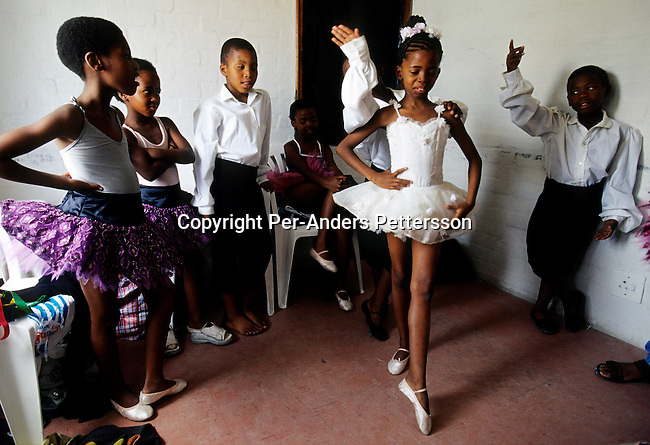 DIDANCE00166.Dance, Eight-year-old Wongi Zoe (c) warms up before a yearly ballet performance on November 25, 2000 in Guguletu, a big township about 10 miles outside Cape Town, South Africa. About 200 children dance ballet in a school called 'Dance For All', which teaches unprivileged children dance after school. Many children are talented and the discipline taught during the dance classes has helped many to improve their concentration in school. The township is struggling with high unemployment, crime and high levels of HIV/Aids and there aren't many opportunities for these children. Tutu, ballet shoe..©Per-Anders Pettersson/iAfrika Photos