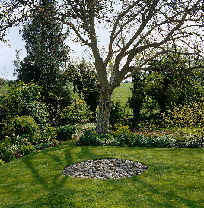 A tranquil corner in an informal English country garden hosts a Zen-like circle of polished pebbles