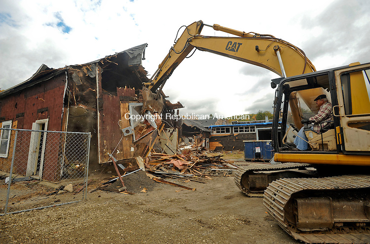 WINSTED, CT-15 OCTOBER 2012--10152JS01-- Gino Cappy with Abcon Environmental of New Haven, tears down a building that used to house The Valley Thrift Shop, as they clear the property to make way for the Carriage Maker Place housing development in Winsted on Monday. The building demolition and clean up should be completed in a couple of months. .Jim Shannon Republican-American