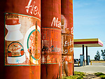 Gas station, weathered, red, big metal tanks pained as Mexican food cans, Helm, California.