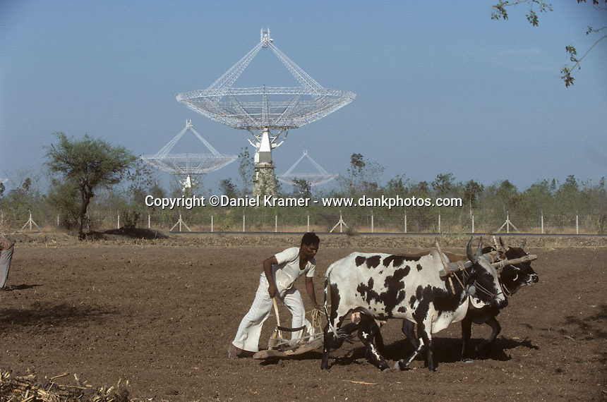 A man uses oxen to plow the soil in front of the Giant Meterwave Radio Telescope in 1996. The GMRT is an array of radio telescopes located near Pune, India. At the time it was built, in 1995, it was world's largest interferometric array.
