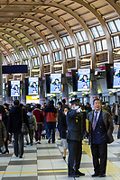 A station worker points out directions to a salarymen in Shinagawa Station, Tokyo, Japan. Friday February 24th 2017
