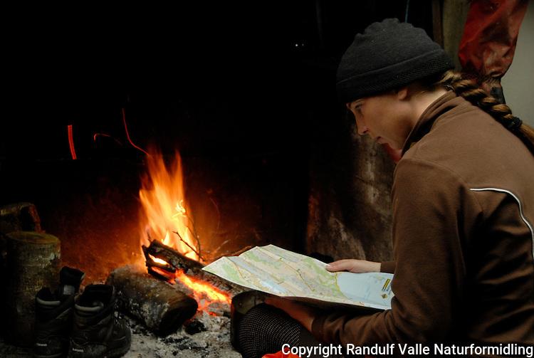 Jente slapper av foran peis med fjellstøvler til tørk ---- Girl relaxing in front of fire place with boots drying by the fire