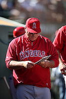 OAKLAND, CA - SEPTEMBER 24:  Manager Mike Scioscia #14 of the Los Angeles Angels looks at his lineup card in the dugout during the game against the Oakland Athletics at O.co Coliseum on Wednesday, September 24, 2014 in Oakland, California. Photo by Brad Mangin
