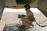 During a flight ferrying British Army personnel to Basrah Air Base, an RAF crewman watches the Iraqi desert from the rear of a Merlin transport helicopter.