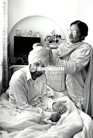 Elderly Asian woman caring for her husband, Nottingham UK 1990