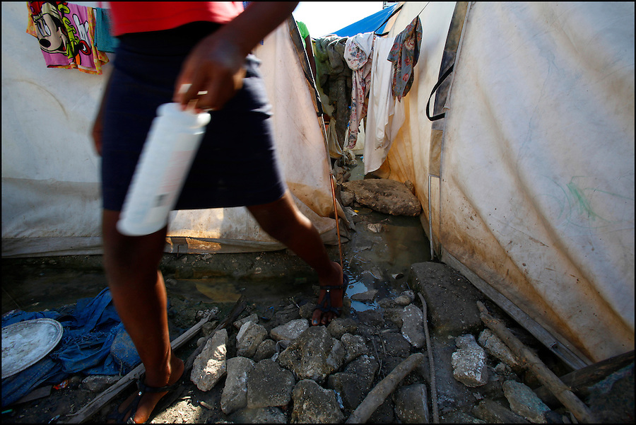 Nov 11, 2010 - Port-au-Prince, Haiti.A resident of a tent city in Port-au-Prince, Haiti steps over stagnant water left behind by Hurricane Tomas that is filled with garbage and possible human waste as she carries a bottle of shampoo to the makeshift showers on Thursday, November 11, 2010 as fears of a Cholera outbreak spread through the area just days after cases of the infection were confirmed in Haiti's capital. Officials from the Pan American Health Organization warn that Haiti's cholera epidemic, spread primarily through consuming infected water and food, is likely to grow much larger in the wake of Hurricane Tomas.  (Credit Image: Brian Blanco)