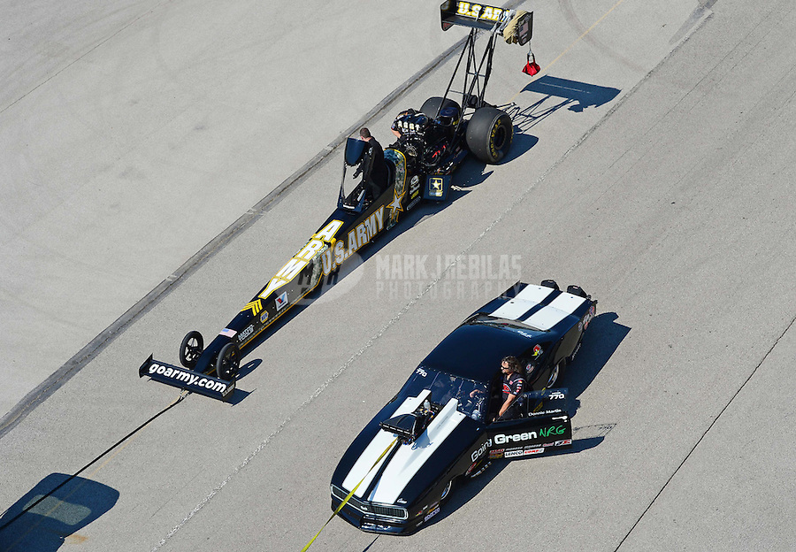 Sept. 29, 2012; Madison, IL, USA: NHRA top fuel dragster driver Tony Schumacher being towed back to the pits passed pro mod driver Donnie Martin during qualifying for the Midwest Nationals at Gateway Motorsports Park. Mandatory Credit: Mark J. Rebilas-