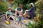 © Joel Goodman - 07973 332324 . 27 July 2013 . Hulme Community Garden Centre , Old Birley Street , Hulme , Manchester M15 , UK . L-R son William Kerruish (six) , father Mark Glass , son Jeremy Kerruish (five) and mother Rachel Kerrruish (all correct) from Old Trafford , playing in the sandpit . Hulme is Where the Art Is festival . Photo credit : Joel Goodman
