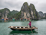 "A fishing village sits on the water in Vietnam's beautiful Ha Long Bay. Ha Long Bay is located on the east coast of Vietnam near Haiphong and contains over 1,900 limestone ""karst"" islands projecting from the sea."