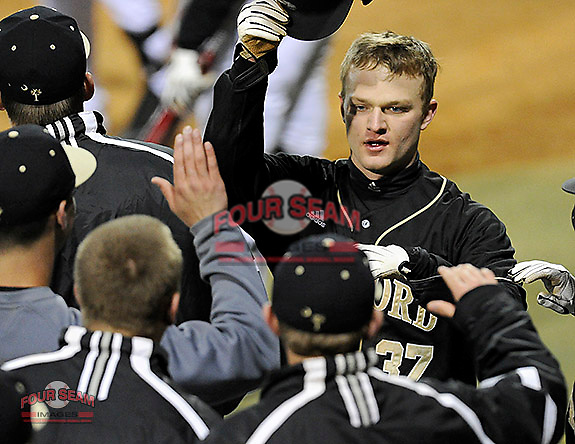 First baseman James Plaisted (37) of the Wofford College Terriers is congratulated by teammates after scoring a run in a game against the Boston College Eagles on Friday, February 13, 2015, at Russell C. King Field in Spartanburg, South Carolina. (Tom Priddy/Four Seam Images)