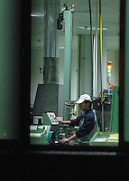 A workers on the production line at 11pm at Taiwanese owned Foxconn plant in Kunshan, (near Shanghai), China. The sprawling plant here employs tens of thousands of workers mostly involved in producing cabling, much of it for Apple Computers and accessories..