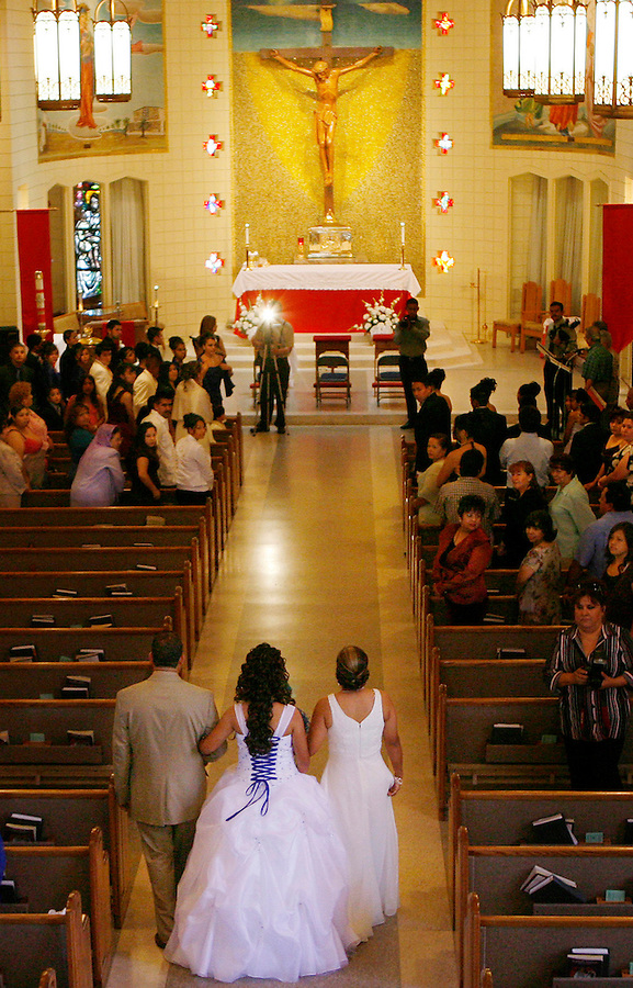 Elizabeth is escorted by her parents Martha and Jose Ureña as she enters mass at Our Lady of Perpetual Help to celebrate her quinceañera.