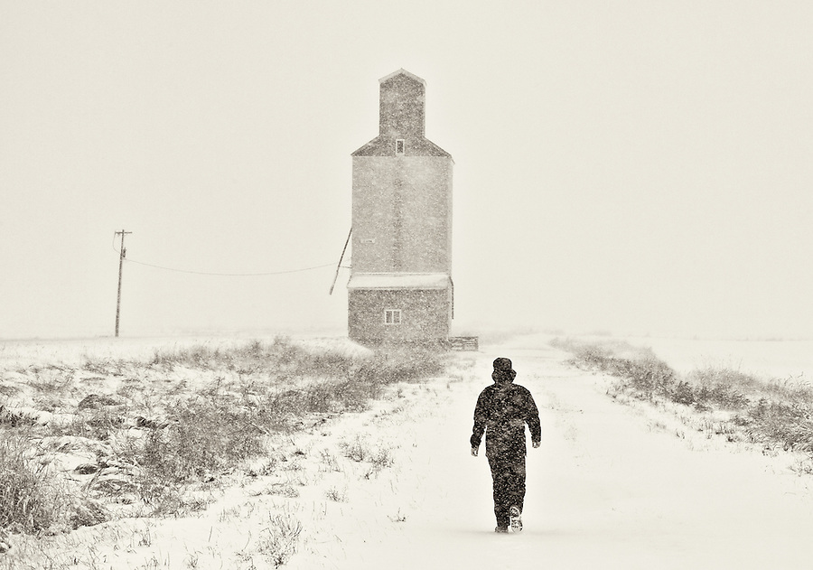 A man walks through a blizzard near a grain elevator on what appears to be a long journey.