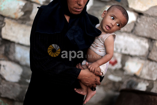 A Palestinian refugee woman carries her baby boy outside their home in one of the poorest regions at al- Zaitoon neighborhood, during the Holy month of Ramadan, in Gaza city, 26 July 2013. Muslims throughout the world are celebrating the fasting month of Ramadan, the holiest month in the Islamic calendar, refraining from eating, drinking, smoking and sexual activities from dawn to dusk. Photo by Ali Jadallah