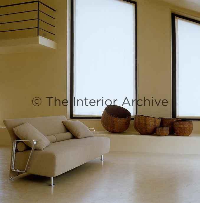 A sofa with metal arms stands in this entrance hall with a collection of ethnic baskets on a ledge beneath the windows