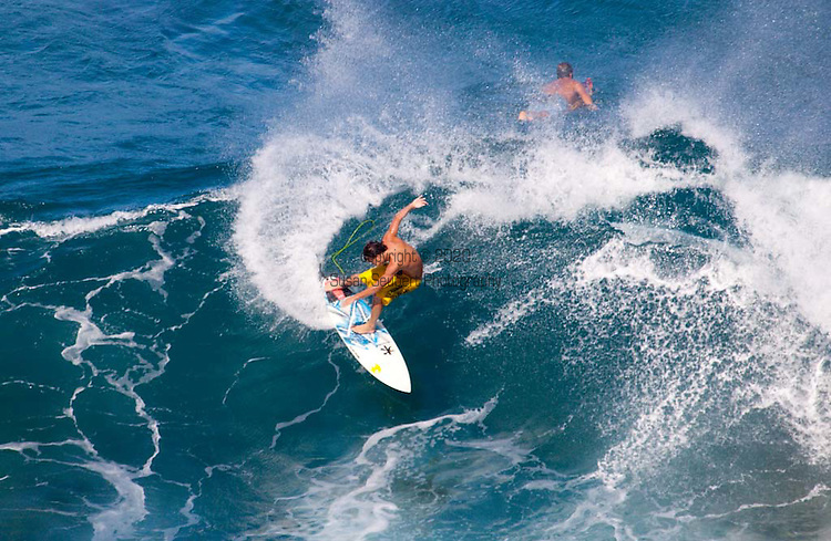 A young man surfing at Windmills, a popular winter break on the North shore of West Maui, HI