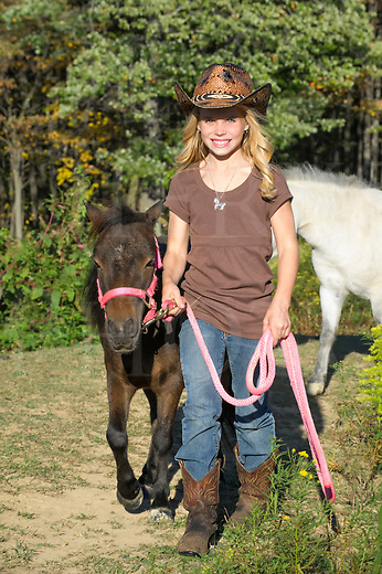 Pretty blonde cowgirl walking her miniature horse toward camera, front view.