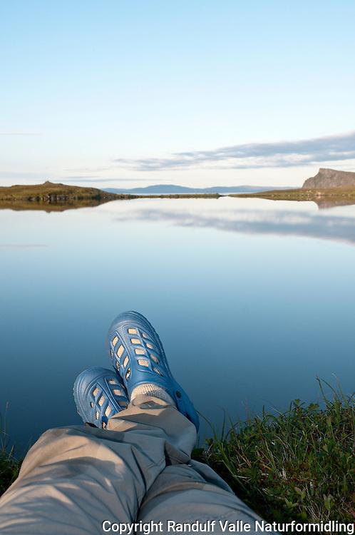Føtter med lette sko foran blikkstille vann. ---- Feet and and lake.