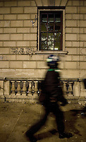 A policeman walks past the Treasury building which has smashed windows and graffiti on the walls after a student demonstration in Westminster, central London on the day the government passed a bill to increase university tuition fees.