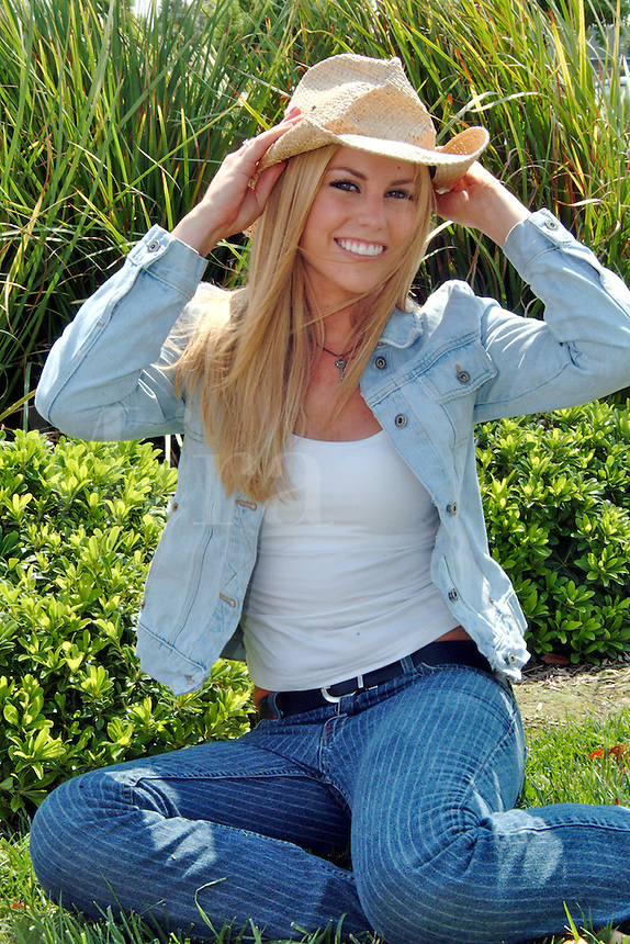 A teenage girl with a big smile and blonde hair wearing a straw cowboy hat, a white top, striped hip hugger jeans, and a blue jacket sits on grass.