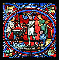 Preparations for the celebratory feast. The father gives orders while a servant cooks in a large pot, another brings a dish and a boy turns the spindle, from the Parable of the Prodigal Son stained glass window, in the north transept of Chartres Cathedral, Eure-et-Loir, France. This window follows the parable as told by St Luke in his gospel. It is thought to have been donated by courtesans, who feature in 11 of the 30 sections. Chartres cathedral was built 1194-1250 and is a fine example of Gothic architecture. Most of its windows date from 1205-40 although a few earlier 12th century examples are also intact. It was declared a UNESCO World Heritage Site in 1979. Picture by Manuel Cohen