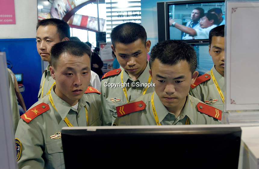 Chinese armed policemen use computers in International High-tech expo in Beijing, China. .