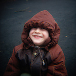 Head and upper torso view of little boy smiling in Winter jacket with hood