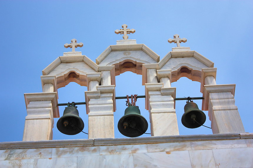 View of a white church's bells under the crosses at Mykonos in Greece