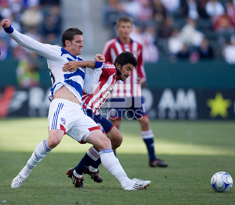 FC Dallas forward Kenny Cooper (33) and Chivas USA midfielder Paulo Nagamura (5) battle for a ball during a MLS match. FC Dallas defeated Chivas USA 2-0 at Home Depot Center Stadium, in Carson, Calif., on Sunday, April 20, 2008.