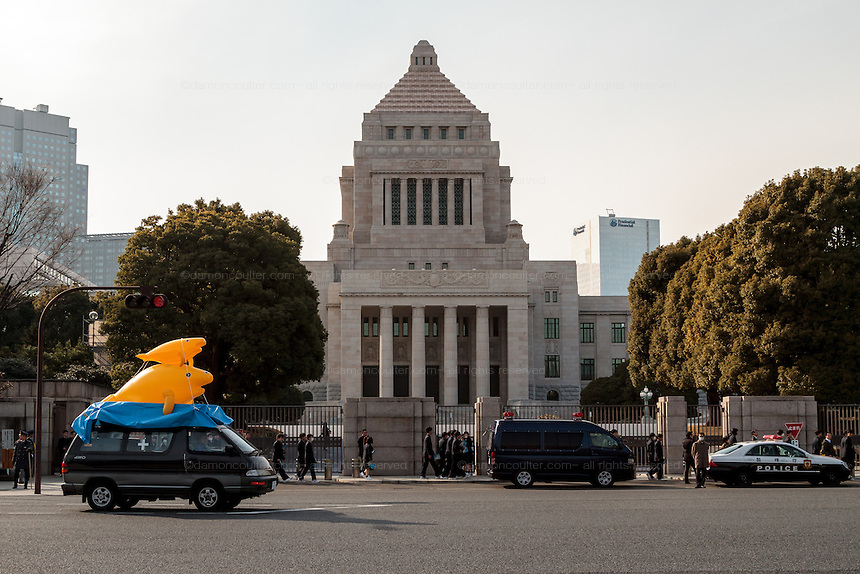 A van with inflatable dugongs on the roof at a rally to protest the construction of a new US military base at Henoko in Okinawa outside the Japanese National Diet building, Nagatacho, Tokyo, Japan Sunday January 25th 2015. Organisers say 7,000 people joined the protest forming a human chain around the Assembly Building.