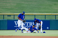 AZL Cubs outfielders Jonathan Sierra (22, left) and Nelson Velazquez (20, right) check on shortstop Luis Vazquez (18) after an awkward landing on a catch in the outfield grass during the game against the AZL Diamondbacks on August 11, 2017 at Sloan Park in Mesa, Arizona. AZL Cubs defeated the AZL Diamondbacks 7-3. (Zachary Lucy/Four Seam Images)