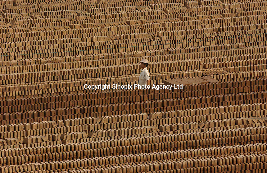 Clay bricks are dried in the sun at a brick factory in Guangzhou, China..20-APR-04