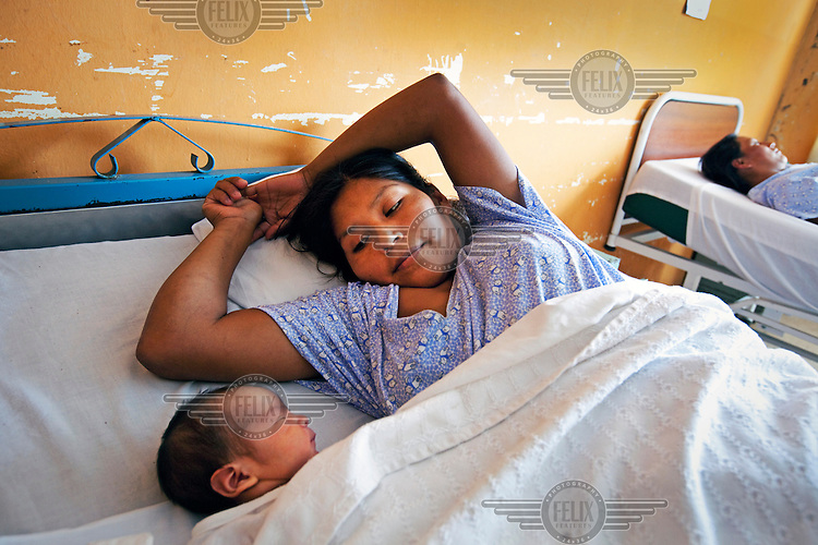 A mother looks at her newly born baby in the maternity ward at a hospital.