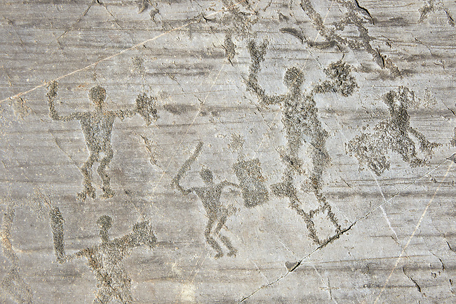 Petroglyph, rock carving, of warriors with swords and shileds. Carved by the ancient Camuni people in the iron age between 1000-1600 BC. Rock no 24,  Foppi di Nadro, Riserva Naturale Incisioni Rupestri di Ceto, Cimbergo e Paspardo, Capo di Ponti, Valcamonica (Val Camonica), Lombardy plain, Italy