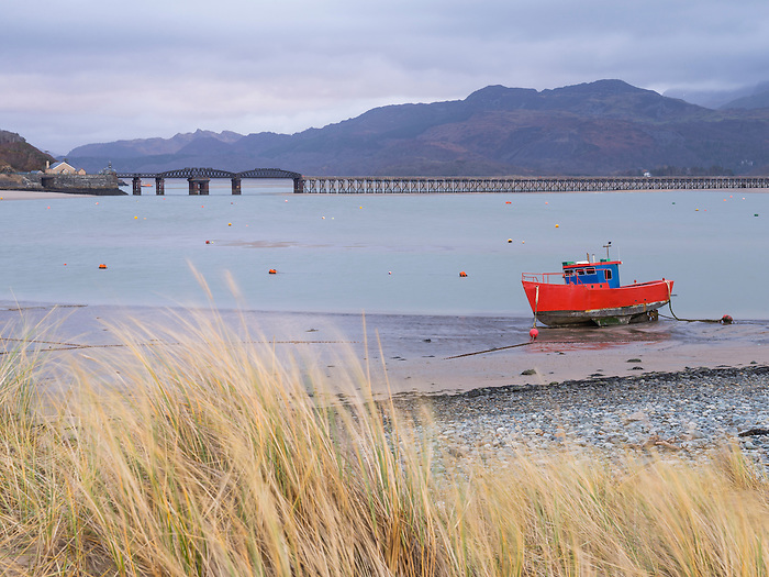 Old fishing boat and Barmouth Bridge in Barmouth Harbour with Cader (Cadair) mountains behind (part of Snowdonia National Park), Gwynedd, North Wales, Wales, United Kingdom, Europe