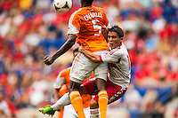 Warren Creavalle (5) of the Houston Dynamo knocks Connor Lade (16) of the New York Red Bulls out of the way going for a header. The New York Red Bulls defeated the Houston Dynamo 2-0 during a Major League Soccer (MLS) match at Red Bull Arena in Harrison, NJ, on June 30, 2013.
