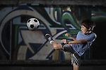 A young boy plays street soccer against a graffiti covered wall - with dramatic lighting and subdued colors - EXCLUSIVELY AVAILABLE on ALAMY http://www.alamy.com/stock-photo-a-young-boy-plays-street-soccer-against-a-graffiti-covered-wall-with-67184260.html