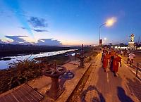 Laos. Monks on a sunset walk along the Mekong near Chao Anouvong Statue.