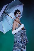 A female model with an umbrella poses at the end of catwalk for the closing  show of the evening at the Fashion & Design Festival