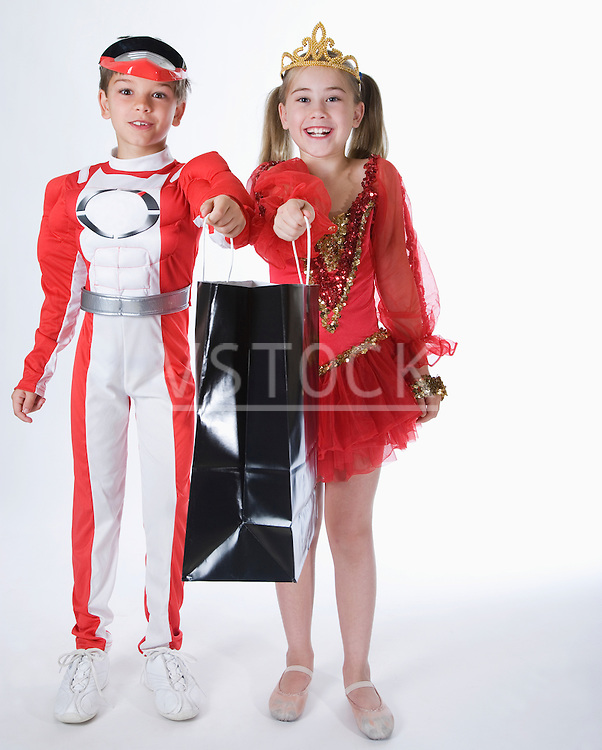 Studio portrait of boy and girl (10-11) wearing costumes and holding gift bag
