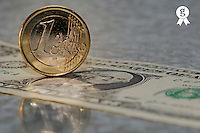 One Euro Coin standing up on US dollar banknote, close-up (Licence this image exclusively with Getty: http://www.gettyimages.com/detail/sb10068346am-001 )