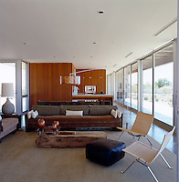 The open-plan main living area is surrounded by sliding glass doors and has furniture made from salvaged Douglas fir
