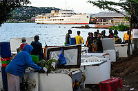 TANZANIA Mwanza, Lake Victoria, ship MV Victoria in port, in front fish seller offer Nile perch / TANSANIA Mwanza, Viktoria See, Schiff MS Victoria im Hafen, im Vordergrund Fischverkaeufer bieten Nilbarsch in alten Gefiertruhen an