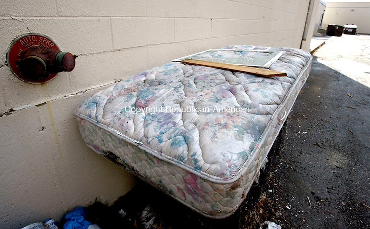 TORRINGTON, CT. 17 February 2012-021712SV02-An old discarded, rain soaked, mattress sits behind the K-Mart plaza in Torrington Friday. The problem of mattress dumping could be coming to an end. Municipalities are proposing legislation to make producers responsible for the cost of disposing mattresses, much like the electronic waste and paint programs in place. Two new mattress-recycling plants are also opening up in the state. .Steven Valenti Republican-American