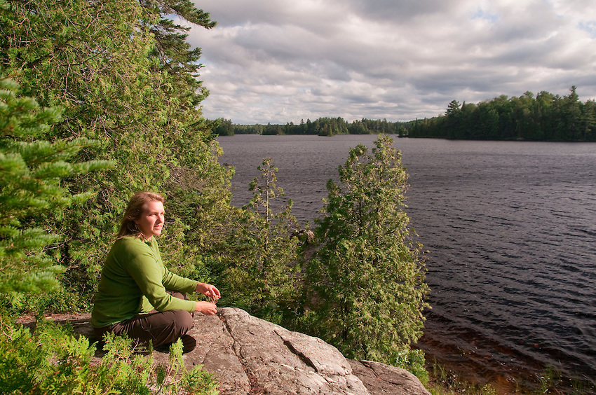 A woman soaks up the silence near her campsite at Craig Lake State Park near Michigamme Michigan.