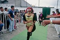Diabolica (foreground) and Amapola the Luchadoras, leave their improvised dressing room and walk through their adoring fans to enter the ring.  Ecatepec, Estado de Mexico. June 2004
