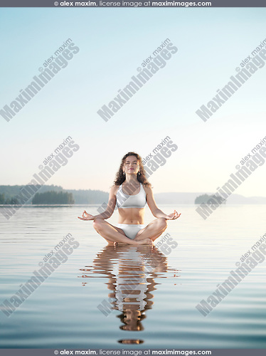 Young woman in white swimsuit meditating. Practicing meditation on a floating platform in calm water on the lake in early morning during sunrise. Yoga meditation. Muskoka, Ontario, Canada.