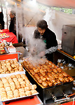 Street food vendor selling grilled bacon wrapped rice balls, Nikumaki Onigiri, Japanese street food market in Kyoto, Japan